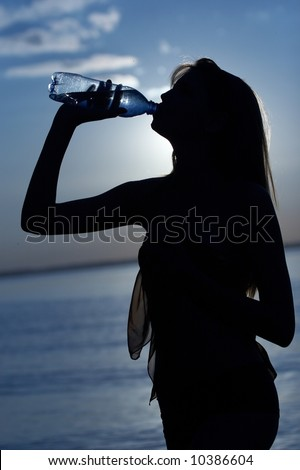 silhouette of girl drink water on water/sky background - stock photo