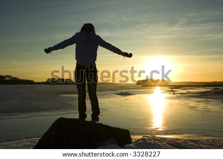 Silhouette of girl having fun by the sea - stock photo