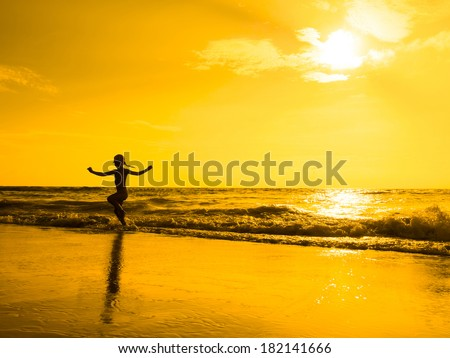 Silhouette of girl jumping on beach at the orange sunset.