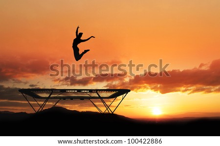 silhouette of girl jumping on trampoline in sunset
