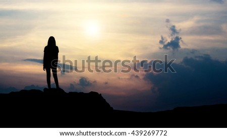 silhouette of girl looking towards the sunset