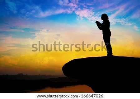 Silhouette of girl praying on the hill - stock photo