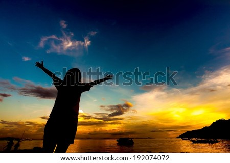 silhouette of girl raising her hands to the sky at dusk - stock photo