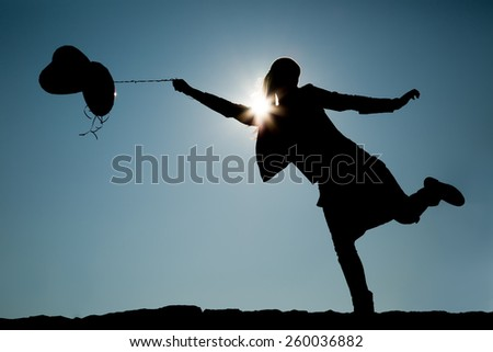 Silhouette of girl with balloons on a string - stock photo
