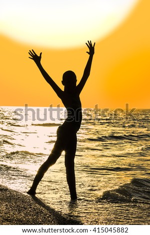 Silhouette of girl with raised hands on the beach on the background of gold sunset - stock photo