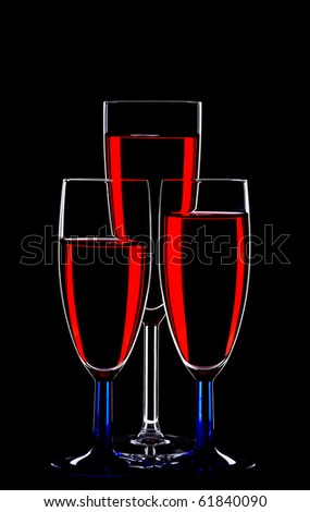silhouette of  glasses filled with red wine over black background.