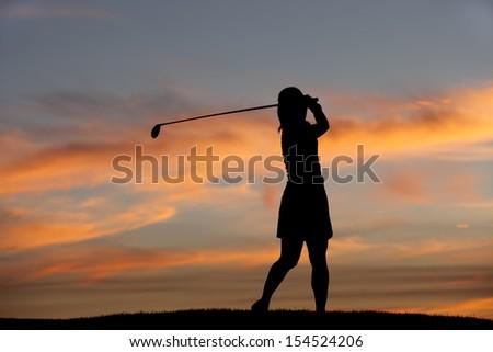 Silhouette of golfer swinging. - stock photo