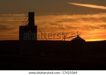 Silhouette of Grain Elevator out on the Prairie at Dusk - stock photo
