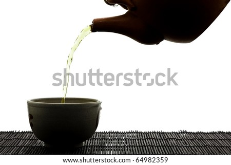SIlhouette of green tea being poured into ceramic cup - stock photo