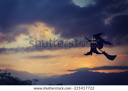 silhouette of halloween witch flying on broomstick in the evening under dramatic sky - Flying Halloween Witch