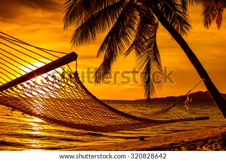 Silhouette of hammock and palm trees on a tropical beach at sunset - stock photo