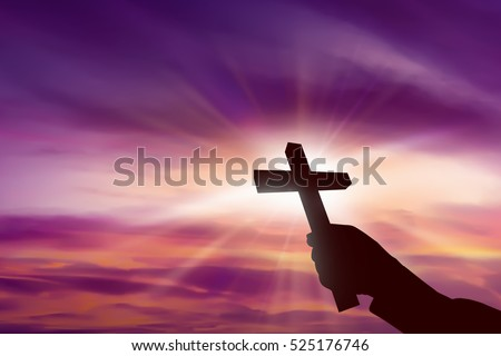 Silhouette of hand holding christian cross over sunset background