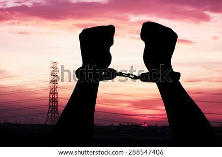 silhouette of hand man in shackle on big sunset background - stock photo
