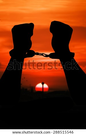 silhouette of hand men in shackle on sunset in city  background - stock photo