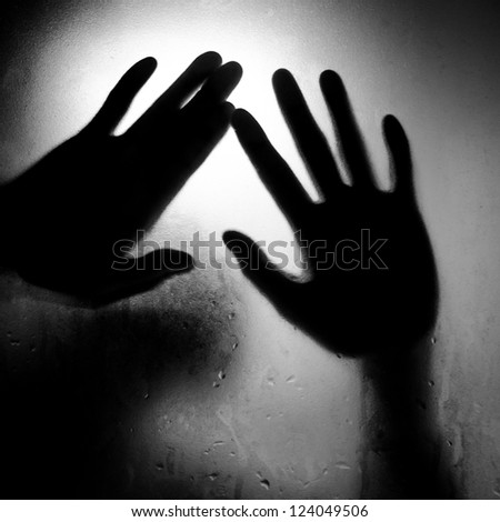 silhouette of hand with glass black and white - stock photo