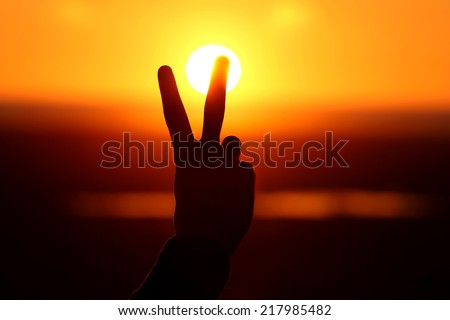 Silhouette of hand with two fingers at sunset  - stock photo