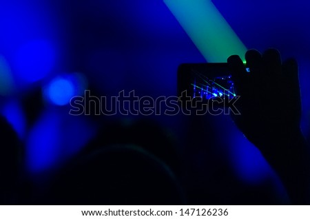 Silhouette of hands holding a mobile phone and taking a video of a rock concert. Low light photos, some grain present.