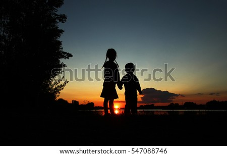 silhouette of happy children on sunset