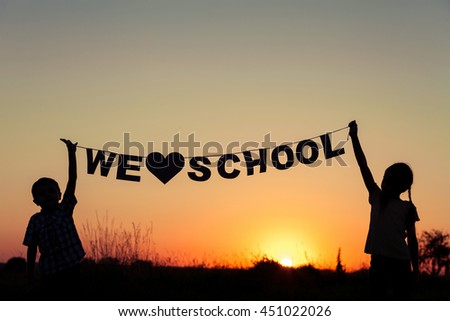 Silhouette of happy children which playing on the field at the sunset time. They having fun on the nature. Concept of the kids are ready to go to school. - stock photo