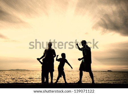 silhouette of happy family at the beach.