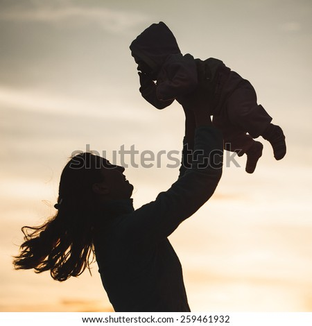 silhouette of happy family mother and child - stock photo