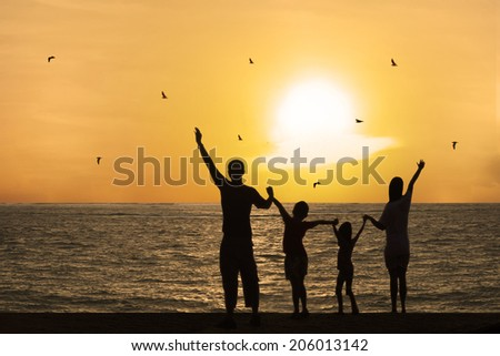 Silhouette of happy family on beach watching sunset together - stock photo