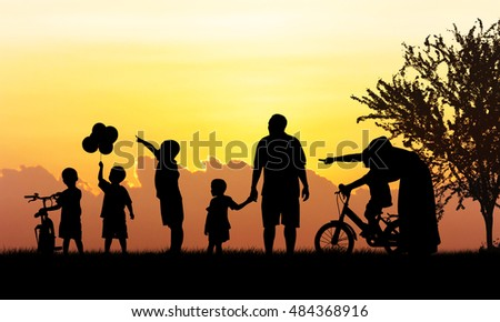 Silhouette of Happy family playing in field sunset background