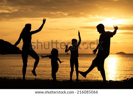 Silhouette of happy family who dancing on the beach at the sunset time. Concept of friendly family.