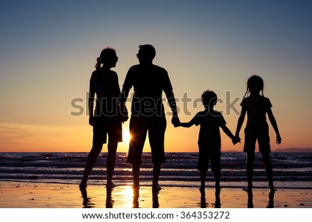 Silhouette of happy family who standing on the beach at the sunset time. Concept of friendly family. - stock photo