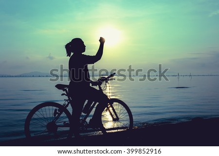 Silhouette of happy female with mountain-bike on colorful blue sky background. Active outdoors lifestyle for healthy concept. Action of winner or successful people.