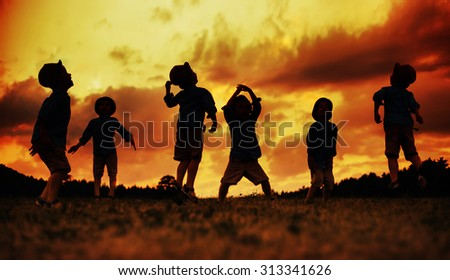 Silhouette of happy kids playing on meadow at sunset