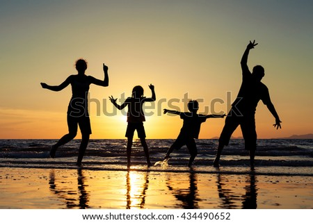 Silhouette of happy people. They are dancing on the beach at the sunset time. Family having fun on the sea. Concept of friendship forever and of summer vacation.