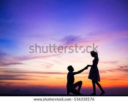 Silhouette of Happy Young Couple Hugging Outside at Sunset,proposing