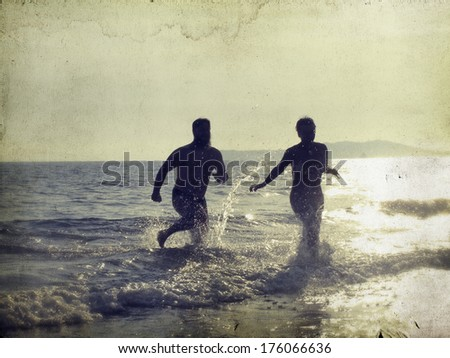 Silhouette of happy young teens playing at the beach on beautiful summer sunset  - stock photo