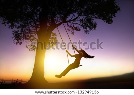 silhouette of happy young woman on a swing with sunset background - stock photo