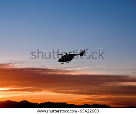 Silhouette of helicopter flying into sunset - stock photo