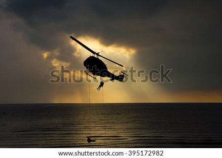 silhouette of helicopter rescue and light sky at sunset. - stock photo