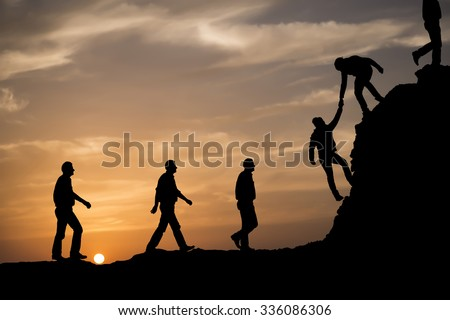 Silhouette of helping hand between two climber - stock photo