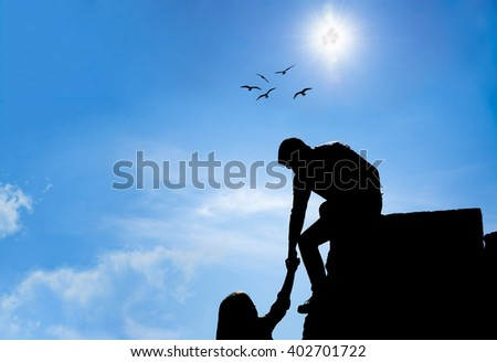 Silhouette of helping hand between two friend