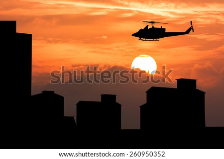 silhouette of high old building and  helicopter fly on sky sunset  background