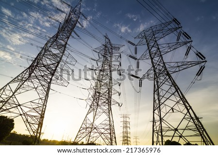 Silhouette of high power transmission towers at sunset