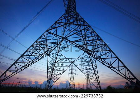 silhouette of high voltage electric pole against beautiful dusky sky use as electric power and energy industry background,backdrop scene - stock photo