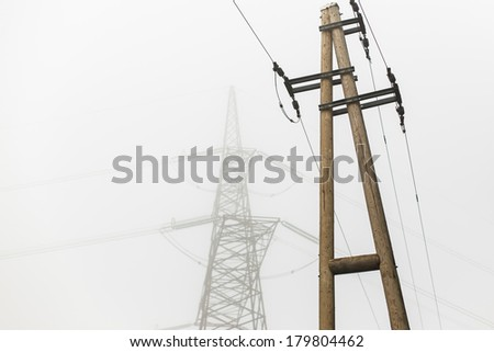Silhouette of high voltage power line against local electric power line - stock photo