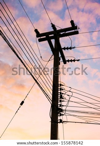 Silhouette of high voltage power lines against colorful sky at sunrise   - stock photo