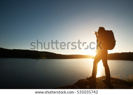 Silhouette of hiker man with backpack in beautiful sunset summer landscape mountain.