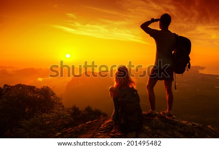 Silhouette of hikers standing on top of hill and enjoying sunrise over the valley - stock photo