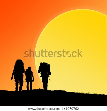 Silhouette of hiking friends against sunset and big sun - stock photo