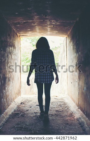 silhouette of hipster woman walk in  tunnel. Light at End of Tunnel - stock photo
