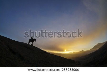 Silhouette of Horsemen during Sunrise at Bromo Indonesia - stock photo