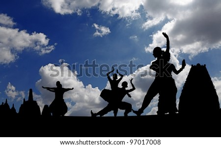 Silhouette of Indian classical dancers posing against Hindu temple against a surreal dramatic cloudy blue sky.